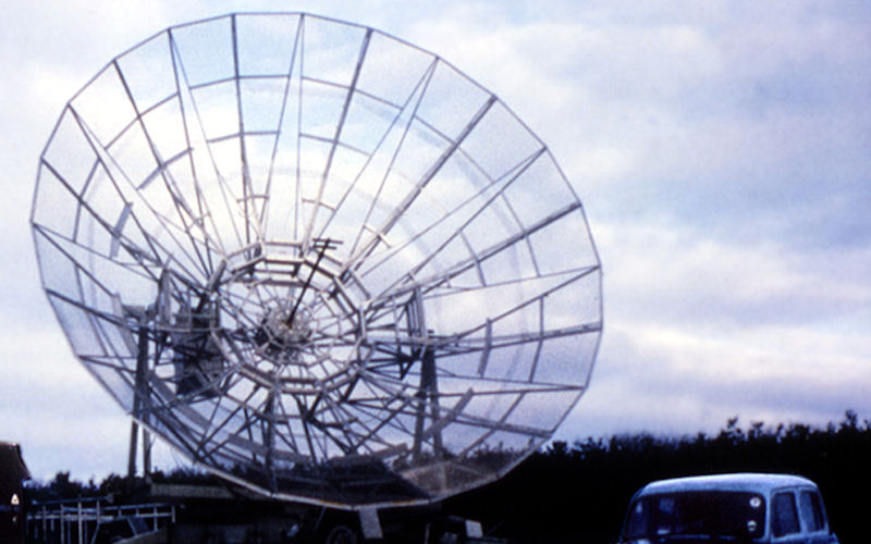 A black and white photograph of a small radio telescope dish.