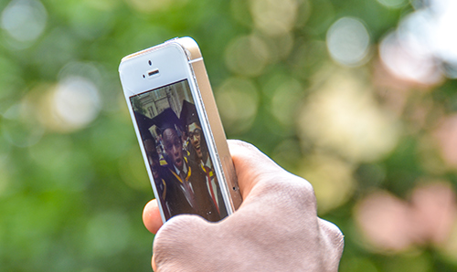 Anonymous hand holding iPhone to take selfie on graduation day