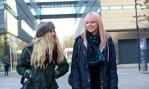 Two female students outside the Alan Turing building
