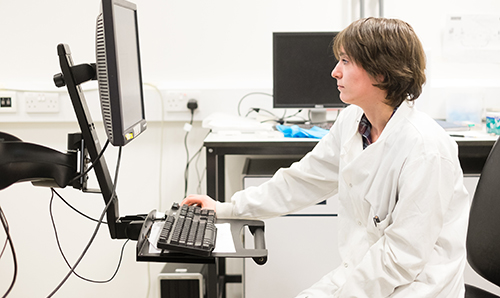 A female researcher in lab coat studying a computer screen