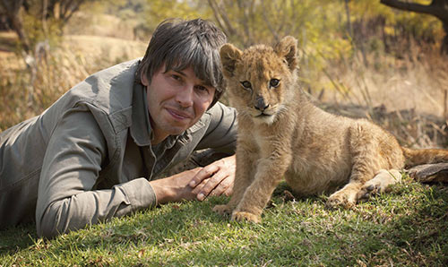 Brian Cox perched on grassy knoll with lion cub