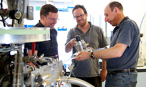 Three male researchers examining equipment in a cryostat laboratory