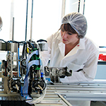 A female student operating accelerator physics equipment