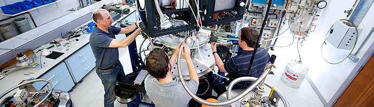 Three researchers operating equipment in the cryostat laboratory