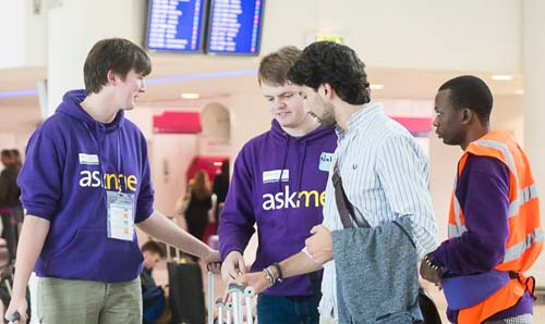 Students in University of Manchester hoodies helping students arriving at an airport