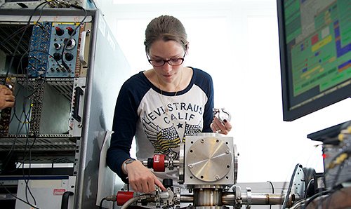 A female postgraduate student looking down at the machinery she is operating