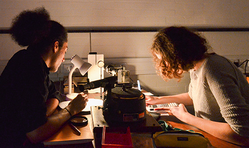 Two undergraduate students focusing under low light while conducting lab experiment
