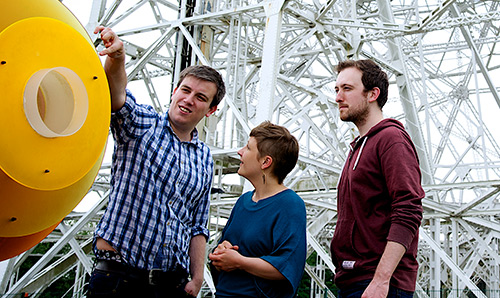 Three students stood in front of the Lovell Telescope