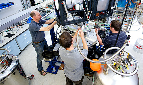 Three male researchers using equipment in the cryostat lab